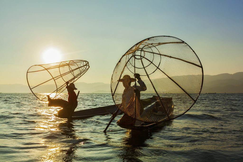 Myanmar travel attraction landmark - two traditional Burmese fishermen at Inle lake, Myanmar famous for their distinctive one legged rowing style on sunrise sunset